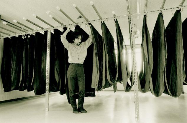 Yohji Yamamoto among fabric rails, Tokyo, 1981<br />